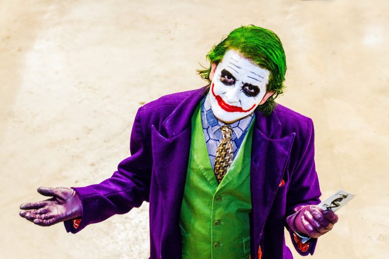 A portrait of a male cosplayer dressed as the joker from the Batman dark Knight movie at a comic con